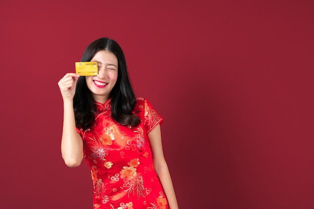 Красивая молодая азиатская женщина носит красное китайское традиционное платье с рукой, держащей кредитную карту, чтобы показать доверие и уверенность для оплаты на сером