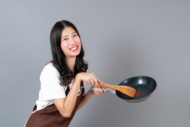 灰色の黒いパンと木のヘラを持っている手でエプロンを着ている美しい若いアジア女性
