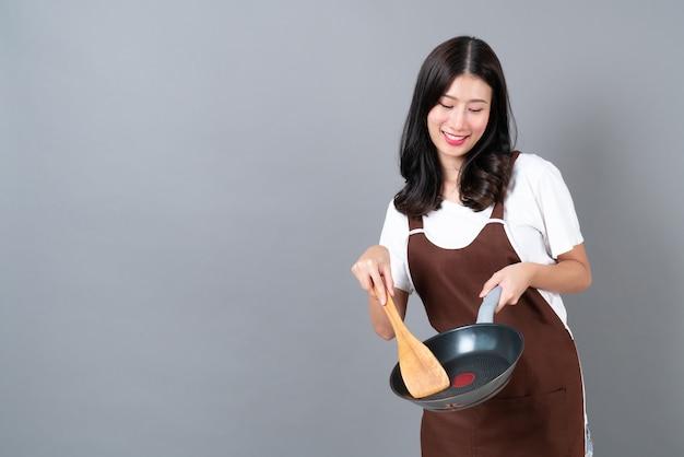 회색에 검은 팬과 나무 주걱을 들고 손으로 앞치마를 입고 아름 다운 젊은 아시아 여자