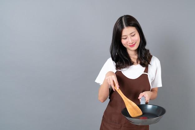 黒い鍋と木製のヘラを持っている手でエプロンを身に着けている美しい若いアジアの女性