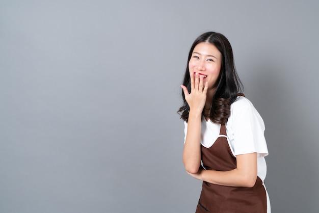 복사 공간 회색에 행복하고 웃는 얼굴로 앞치마를 입고 아름 다운 젊은 아시아 여자