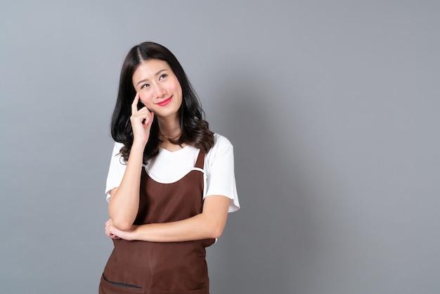 복사 공간 행복하고 웃는 얼굴로 앞치마를 입고 아름 다운 젊은 아시아 여자
