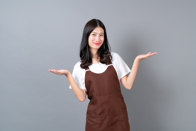 행복하고 웃는 얼굴로 앞치마를 입고 아름 다운 젊은 아시아 여자
