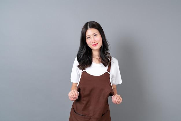 幸せで笑顔のエプロンを身に着けている美しい若いアジアの女性