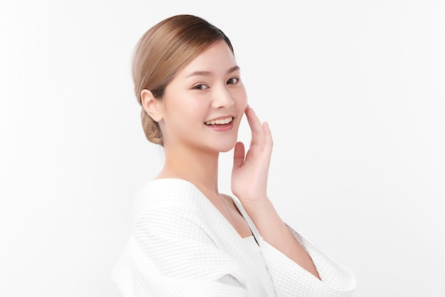 白い背景、フェイスケア、フェイシャルトリートメント、美容、美容、スパのコンセプトにバスローブを着ている美しい若いアジアの女性。