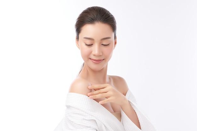白い背景、フェイスケア、フェイシャルトリートメント、美容、美容、スパのコンセプトにバスローブを着ている美しい若いアジアの女性。 Premium写真