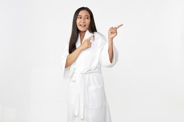 バスローブを着ている美しい若いアジアの女性は、清潔で新鮮な肌の笑顔で幸せと陽気な、白い背景で隔離の前向きな感情