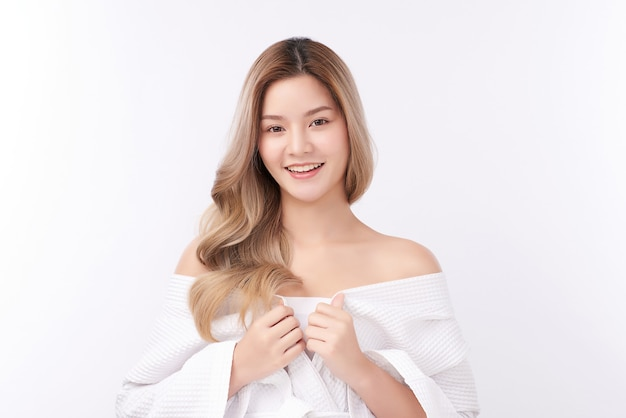 Beautiful young asian woman wearing bathrobe on white background, face care, facial treatment, cosmetology, beauty and spa concept.