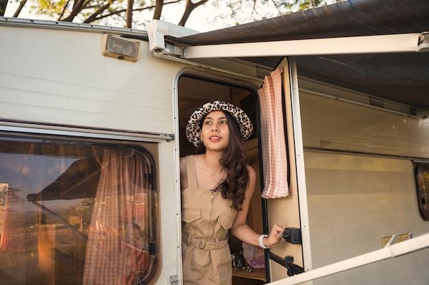 휴가 캠프장에서 모터 홈에서 놀고 모자를 쓰고 아름 다운 젊은 아시아 여자