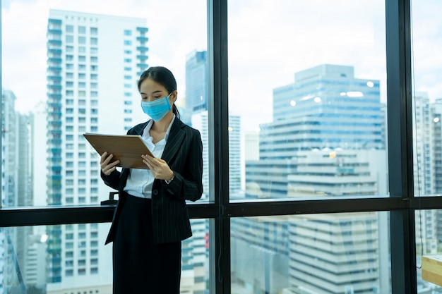 Beautiful young asian woman wearing protective mask to protect against covid-19 working in office in modern office.