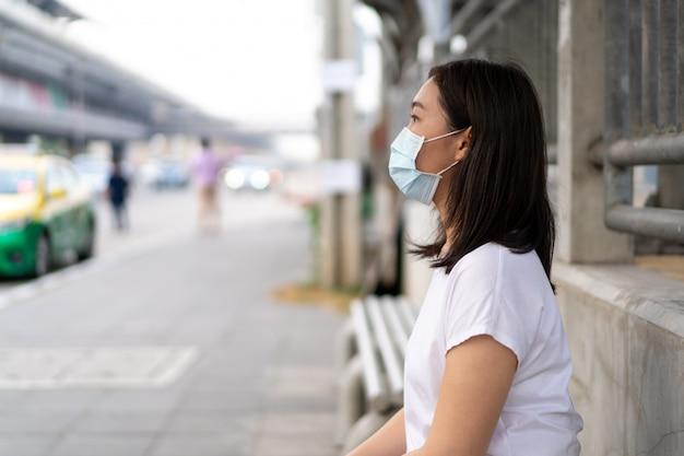 完全に大気汚染pm2.5で街を旅行中に防護マスクを身に着けている美しい若いアジア女性。世界で重大なcovid19疾患、covid-19を保護するために衛生マスクを着用している女性