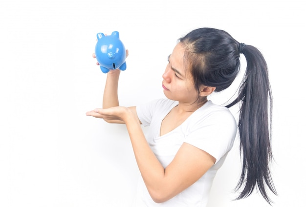 Beautiful young asian woman on white background with hand holding piggy bank. finance savings and money wealth or extravagant concept. copy space.