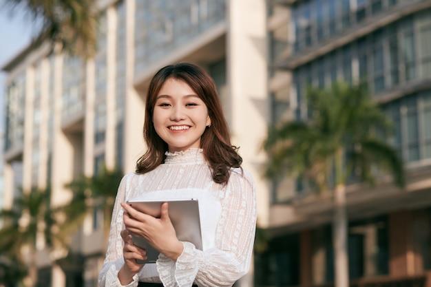 タブレット コンピューターを見る美しい若いアジア女性