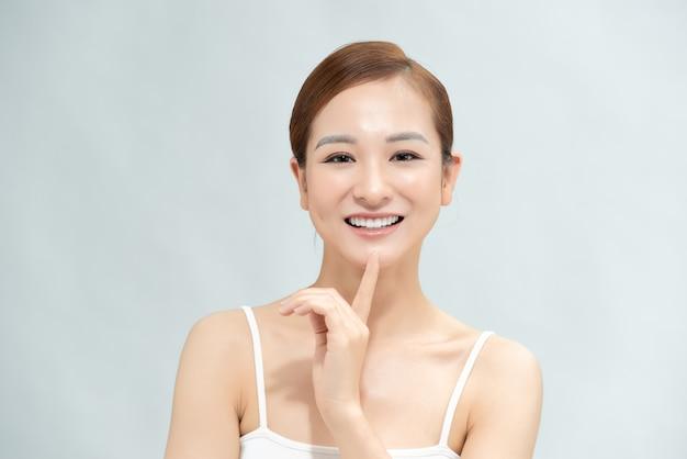 Красивая молодая азиатская женщина с чистой свежей кожей касается ее лица, ухода за лицом, косметологии, красоты и спа,