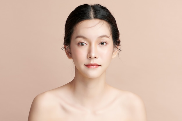 ベージュの背景、フェイスケア、フェイシャルトリートメント、美容、美容とスパ、アジアの女性の肖像画にきれいな新鮮な肌を持つ美しい若いアジアの女性。