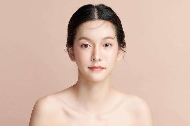 베이지색 배경에 깨끗하고 신선한 피부를 가진 아름다운 젊은 아시아 여성, 얼굴 관리, 얼굴 치료, 미용, 미용 및 스파, 아시아 여성 초상화.