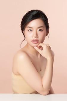 ベージュのきれいな新鮮な肌を持つ美しい若いアジアの女性
