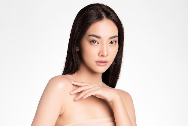 ピンクの背景、フェイスケア、フェイシャルトリートメントで、きれいな新鮮な肌を持つ美しい若いアジアの女性。美容、美容、スパ。アジアの女性の肖像画