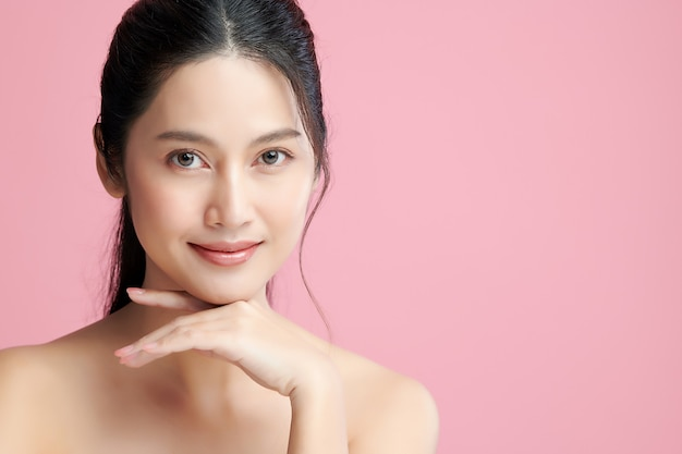 ピンクの背景、フェイスケア、フェイシャルトリートメント、美容、美容とスパ、アジアの女性の肖像画にきれいな新鮮な肌を持つ美しい若いアジアの女性。