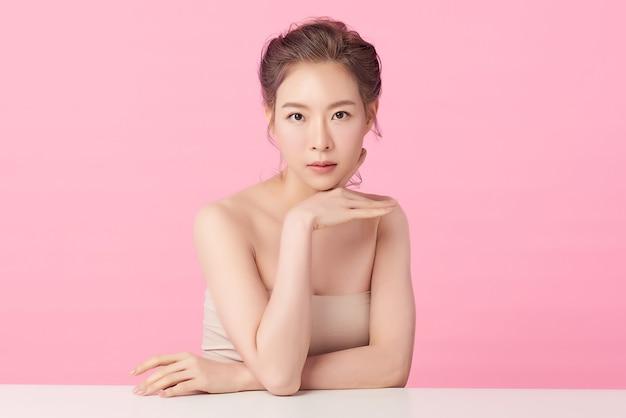 清潔でさわやかな肌、ピンクの背景、顔のケア、フェイシャルトリートメントと美しい若いアジア女性。美容、美容