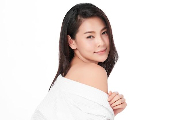 ピンクの背景に、きれいな新鮮な肌を持つ美しい若いアジアの女性