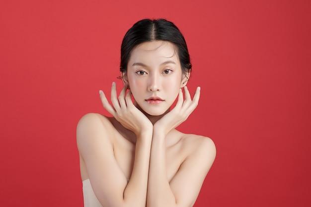 赤い背景、フェイスケア、フェイシャルトリートメント、美容、美容とスパ、アジアの女性の肖像画にきれいな新鮮な肌を持つ美しい若いアジアの女性。