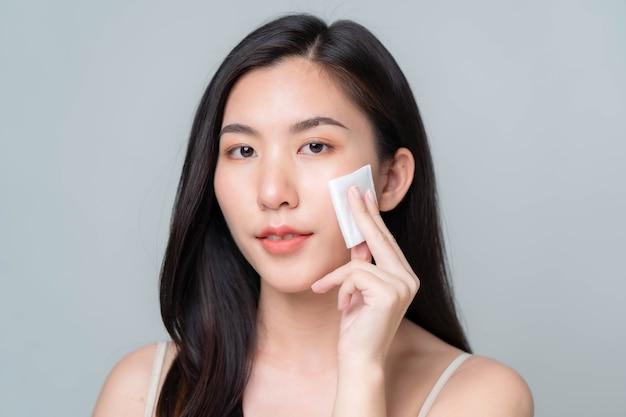 배경에 깨끗하고 신선한 피부를 가진 아름 다운 젊은 아시아 여자. 아시아 여성 초상화입니다.