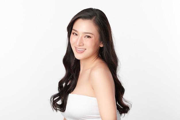 白い背景、フェイスケア、フェイシャルトリートメント、美容、美容とスパ、アジアの女性の肖像画にきれいな新鮮な肌を持つ美しい若いアジアの女性。