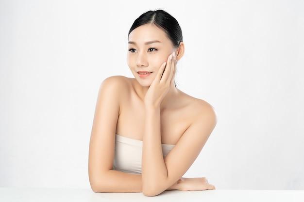 白い背景、顔のケア、フェイシャルトリートメント、美容、美容上のきれいな新鮮な肌と美しい若いアジア女性