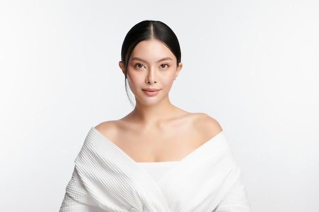 白い背景のきれいな新鮮な肌を持つ美しい若いアジアの女性フェイスケアフェイシャルトリートメント