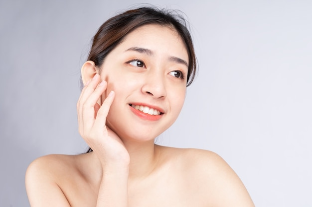 白い背景のきれいな新鮮な肌を持つ美しい若いアジアの女性、