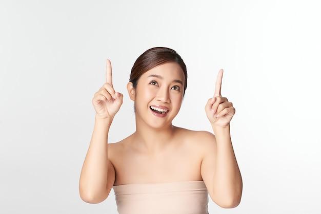 위쪽을 가리키는 흰색에 깨끗하고 신선한 피부를 가진 아름 다운 젊은 아시아 여자