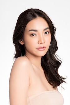 白い壁にきれいな新鮮な肌を持つ美しい若いアジアの女性、フェイスケア、フェイシャルトリートメント、美容、美容とスパ、アジアの女性の肖像画
