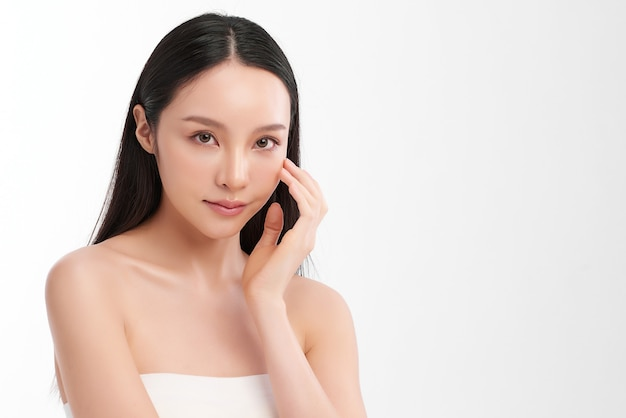 白い壁にきれいな新鮮な肌を持つ美しい若いアジアの女性、フェイスケア、フェイシャルトリートメント、美容、美容とスパ、アジアの女性の肖像画。