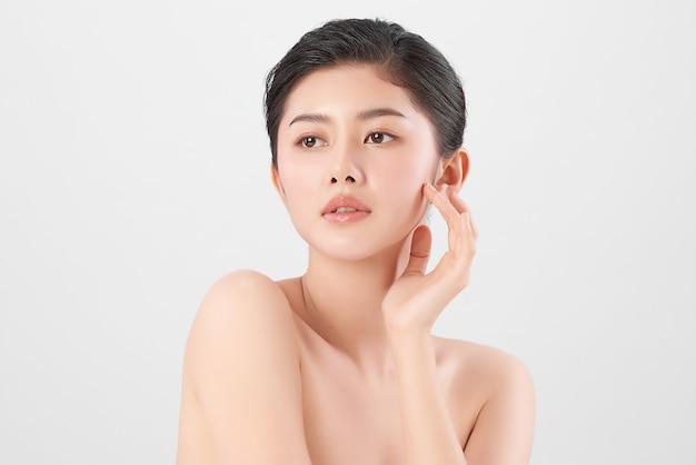 Красивая молодая азиатская женщина с чистой свежей кожей на белом