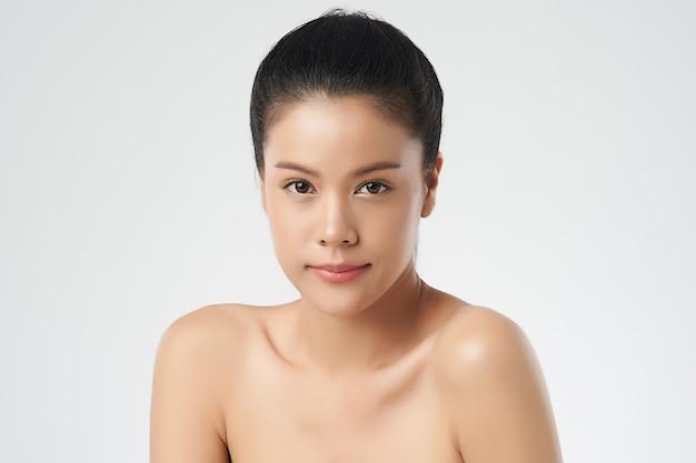 清潔でさわやかな肌のポーズと美しい若いアジア女性