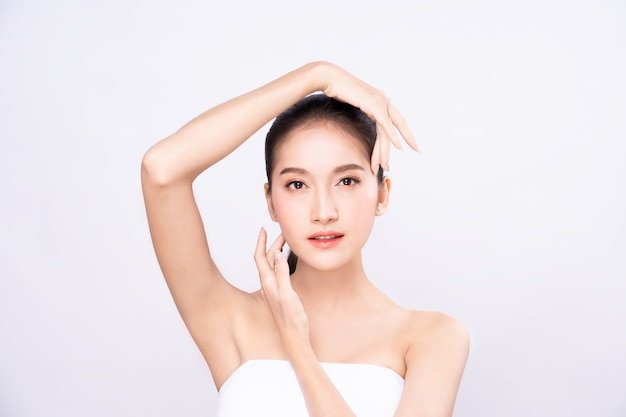 Beautiful young asian woman with clean fresh skin touching two hands on face in beauty pose.