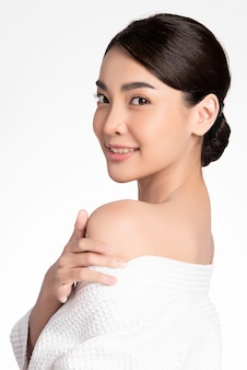 Beautiful young asian woman with clean fresh skin on white wall, face care, facial treatment, cosmetology, beauty and spa, asian women portrait
