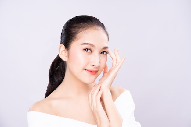 Beautiful young asian woman with clean fresh white skin face in beauty pose touching shoulder with finger.