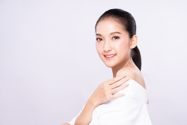 Beautiful young asian woman with clean fresh white skin face in beauty pose touching shoulder with finger