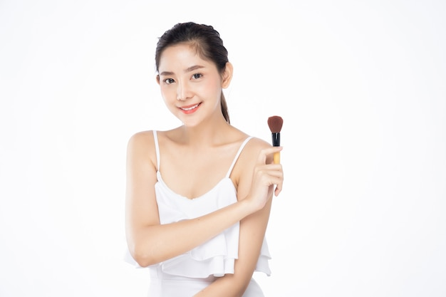 Beautiful young asian woman with clean fresh white skin holding brush on with one hand, beauty pose.