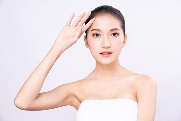 Красивая молодая азиатская женщина при чистая свежая белая кожа поднимая ее руку и руку в солнечности защиты в изолированной белой предпосылке.