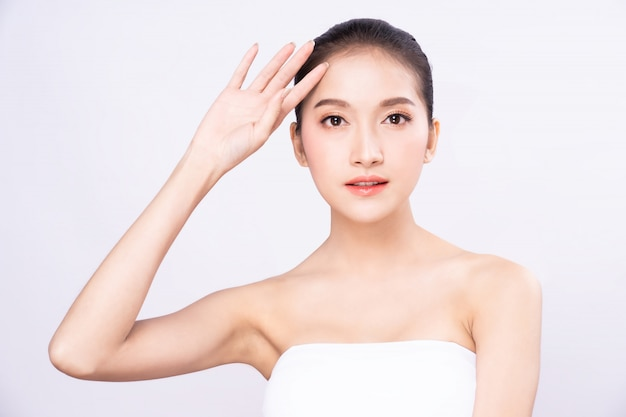 Beautiful young asian woman with clean fresh white skin raising her arm and hand in protection sunshine in isolated white background.