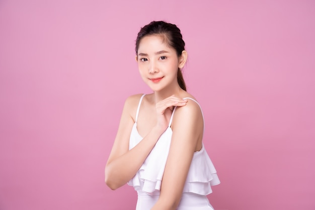Beautiful young asian woman with clean fresh white skin soft touch shoulder in beauty pose. girl smiling in isolated background. facial treatment, cosmetic, make up and surgery advertisement