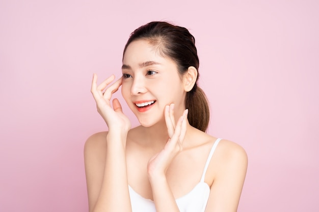 Beautiful young asian woman with clean fresh white skin touching her own face softly in beauty pose touching with fingers in pink background.