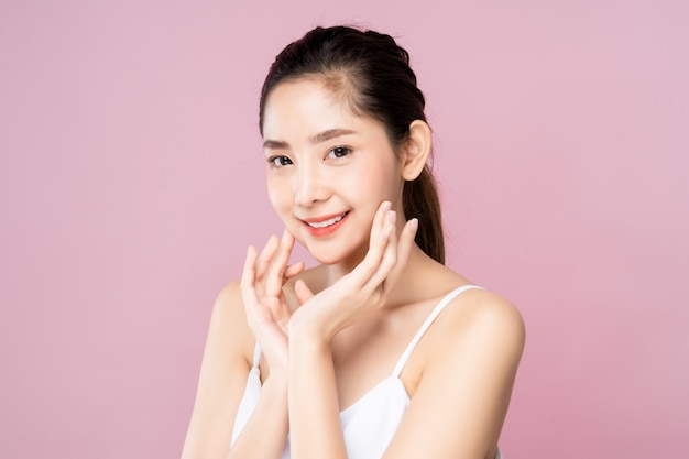 Beautiful young asian woman with clean fresh white skin touching her own face softly in beauty pose.