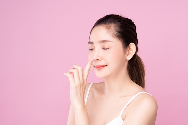 Beautiful young asian woman with clean fresh white skin touching her own nose softly with fingers in beauty pose.