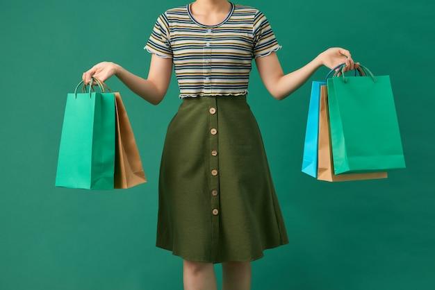 緑の上の色の買い物袋を持つ美しい若いアジアの女性