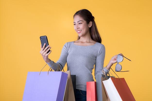Красивая молодая азиатская женщина с красочными сумками и смартфоном, изолированными на желтом backgroun