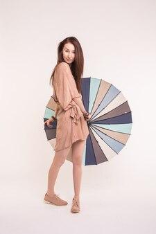 白の明るいドレスでカラフルな傘を持つ美しい若いアジアの女性